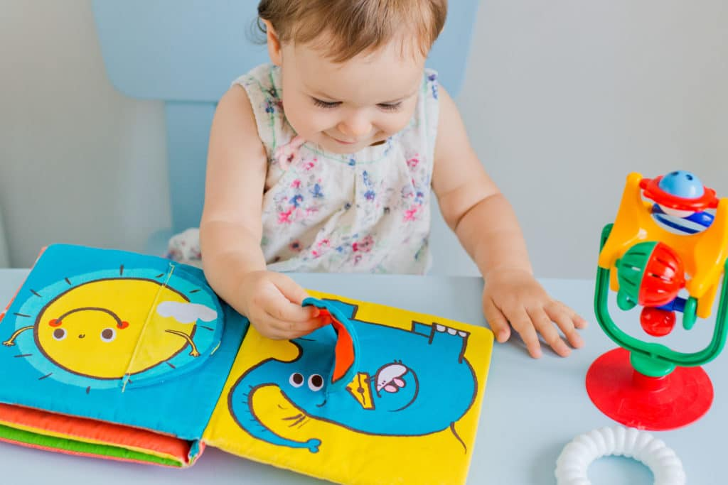small child playing with soft developmental book